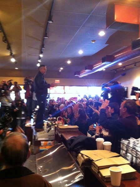 Huntsman standing on a counter filled with muffins.  Packed house in coffee shop